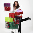 Womwith cart full of gifts — Stock Photo #16783627