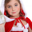 Little girl in Christmas outfit offering a present — Стоковая фотография