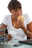 Hungry female executive eating hamburger — Stock Photo