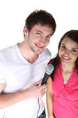 Couple sharing a microphone — Stock Photo