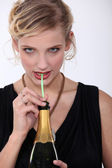 Woman drinking champagne through a straw — Stock Photo