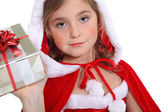 Little girl in Christmas outfit offering a present — Stock Photo