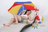 魅力的な女性はビーチでサンラウン ジャーに横になっています。 — ストック写真