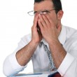 Tired young businessman rubbing his eyes — Stock Photo #16795003