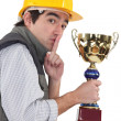 Secretive construction worker with a trophy — Stock Photo