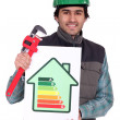 Plumber holding wrench and energy rating sign - Stock Photo