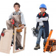Two children acting out adult trades - carpentry and construction - Stock Photo
