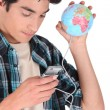 Man holding mobile telephone and miniature globe — Stock Photo #16799631