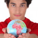 Teenage boy holding a mini-globe — Stock Photo #16799683
