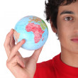 Young man holding a globe — Stock Photo #16799713