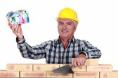 Tradesman holding up a house model make out of money — Stock Photo