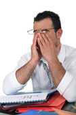 Tired young businessman rubbing his eyes — Stock Photo
