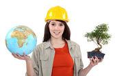 Girl holding a globe and a bonsai — Stock Photo