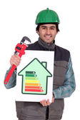 Plumber holding wrench and energy rating sign — Stock Photo