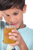 Young boy tasting some honey — Stock Photo