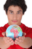 Teenage boy holding a mini-globe — Stock Photo
