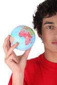 Young man holding a globe — Stockfoto