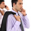 Two young businessmen holding jackets over shoulders — Stock Photo