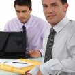 Two business colleagues sat at desk - Stockfoto