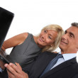 Mature business couple with a laptop — Stock Photo #16805967
