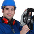 A manual worker with a circular saw. - Stockfoto
