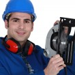 Stock Photo: Manual worker with circular saw.