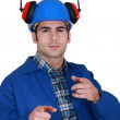 Portrait of helmeted craftsmwith earmuffs showing off — Stock Photo #16807225