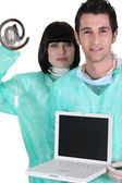 Medical workers holding a laptop and an at sign — Stock Photo