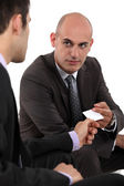 Two businessmen exchanging cards — Stock Photo