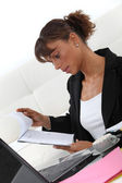 Businesswoman looking at a notepad — Stockfoto