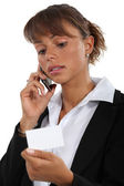 Businesswoman holding a visit card and talking on her cell — Stockfoto