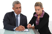Blond assistant helping boss — Stock Photo