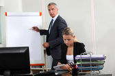 Businessman stood by flip-chart — Stockfoto