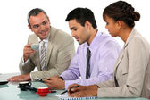 Three businesspeople discussing over coffee. — Stock Photo