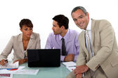 Three business colleagues at a desk — Stock Photo