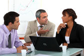 Three in animated business meeting — Stock Photo