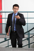 Businessman on the stairwell with a cellphone — Stock Photo