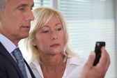 Man showing mobile phone to woman — Foto Stock