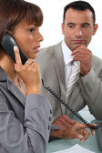 Man observing his colleague on the phone — Stock Photo