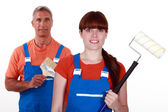 Painters in overalls holding brushes — Stockfoto
