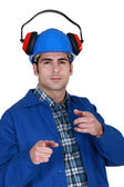 Portrait of helmeted craftsman with earmuffs showing off — Stock Photo
