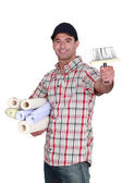 Man holding rolls of wallpaper — Stock Photo