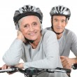 An elderly couple riding their bikes together — Stock Photo