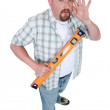 Stock Photo: Builder with spirit-level holding hand to ear