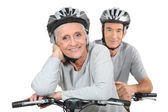 An elderly couple riding their bikes together — Photo