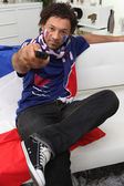 French football fan with a remote control — Stock Photo
