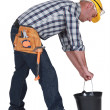 Worker lifting plastic bucket — Stock Photo
