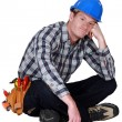 Stock Photo: Bored manual worker sat cross-legged