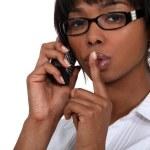 Black businesswoman making hush gesture during phone call — Stock Photo
