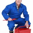 Senior craftsman holding a spanner and a tool box — Stock Photo